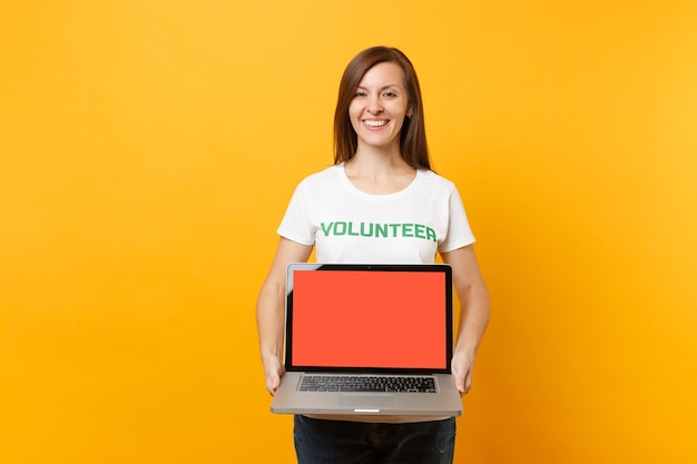 Woman in white t-shirt written inscription green title volunteer hold laptop pc computer, blank empty screen isolated on yellow background. voluntary free assistance help, charity grace work concept.