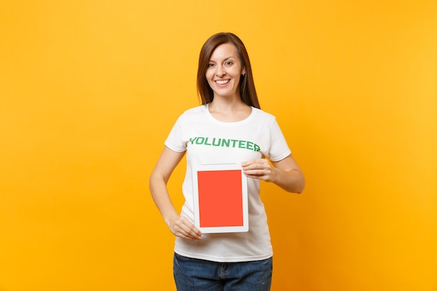 Woman in white t-shirt written inscription green title volunteer hold tablet pc computer, blank empty screen isolated on yellow background. voluntary free assistance help, charity grace work concept.