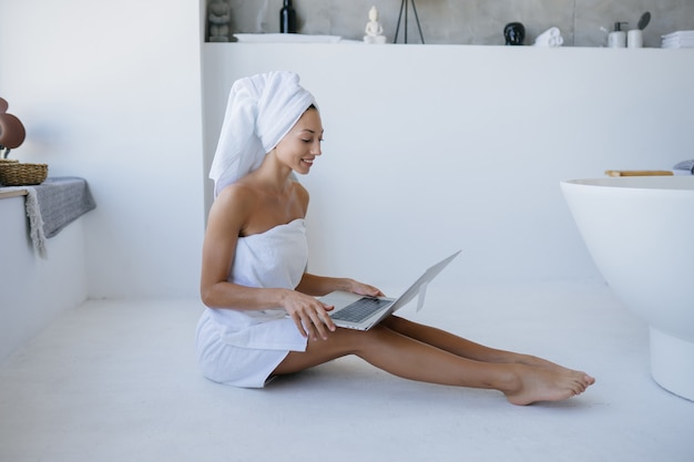 Woman in white towel sits in the bathroom and use a laptop.