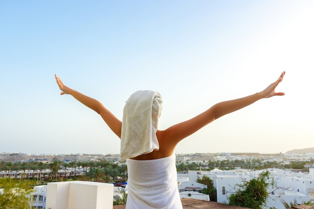 A woman in a white towel stands on the terrace with her hands up from happiness with a view of the mountains in the hotel room