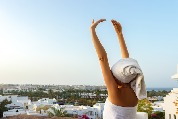 Woman in a white towel stands on the terrace with her hands up