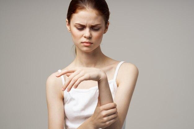 Woman in white tshirt arm pain arthritis chronic disease light background