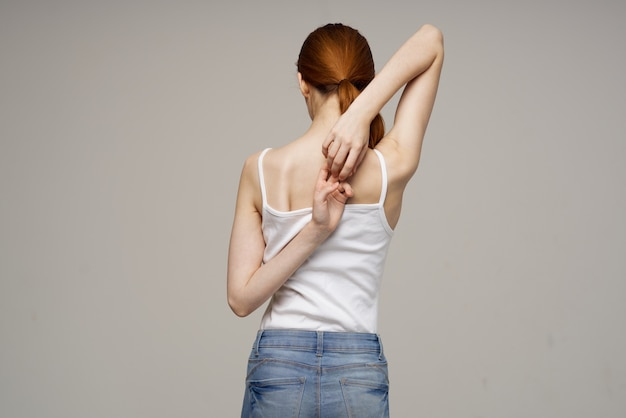 Woman in white tshirt back pain health problems osteoporosis studio treatment