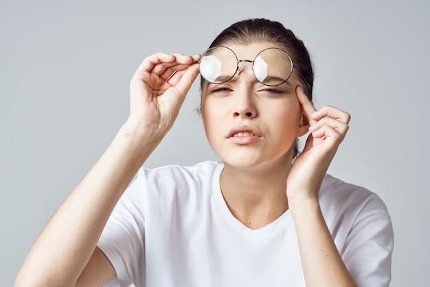 Woman in white tshirt glasses poor eyesight closeup