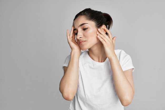 Woman in white tshirt holding face dissatisfaction problem isolated background