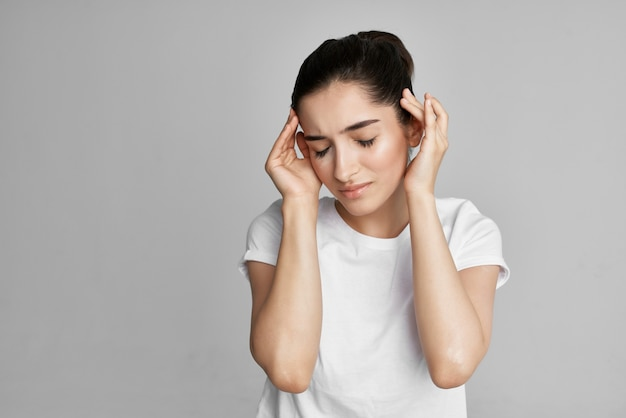 Woman in white tshirt holding her head headache upset