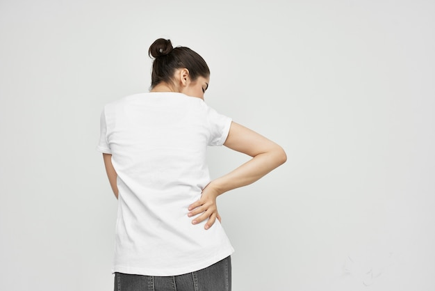 Woman in white tshirt holding her lower back back pain
