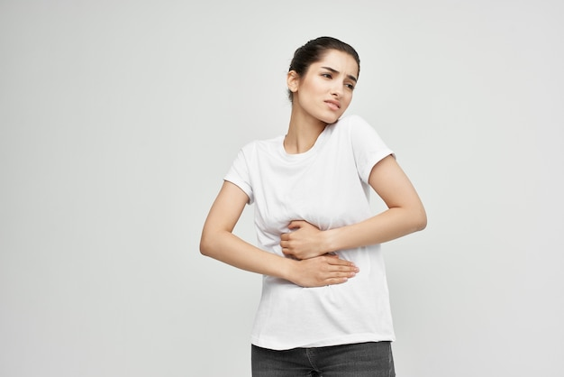 Woman in white tshirt holding her stomach diarrhea pain health problems