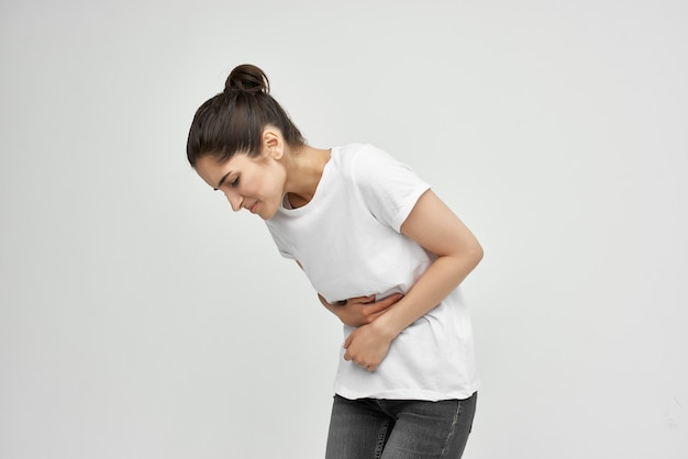 Woman in white tshirt holding her stomach health problems diarrhea abdominal pain