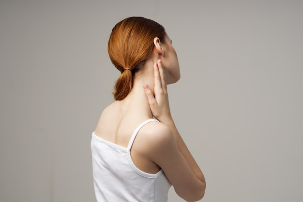 Woman in white tshirt holding on to the neck health problems joint light background