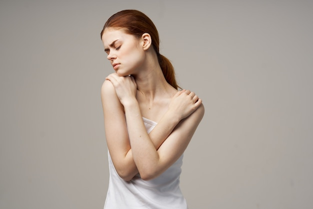 Woman in white tshirt holding on to the neck health problems joint studio treatment