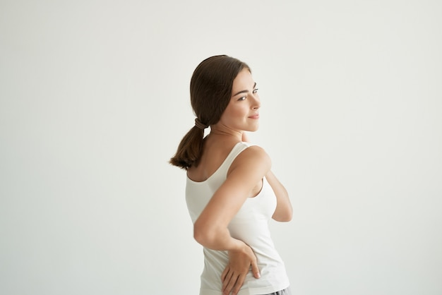 Woman in white tshirt joint pain treatment health light background