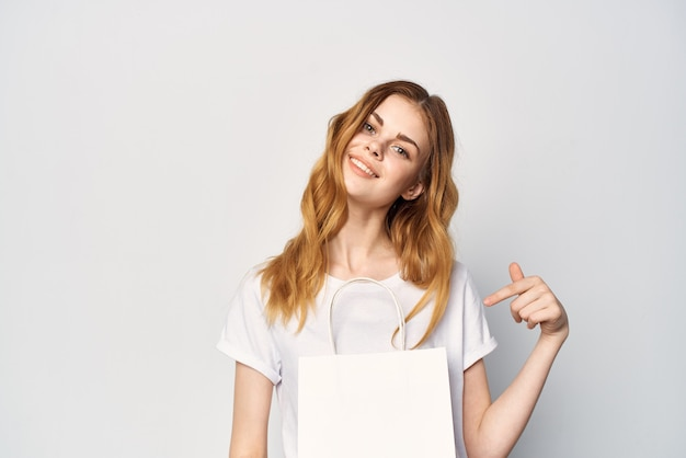 Woman in white tshirt package in hands gift shopping light background
