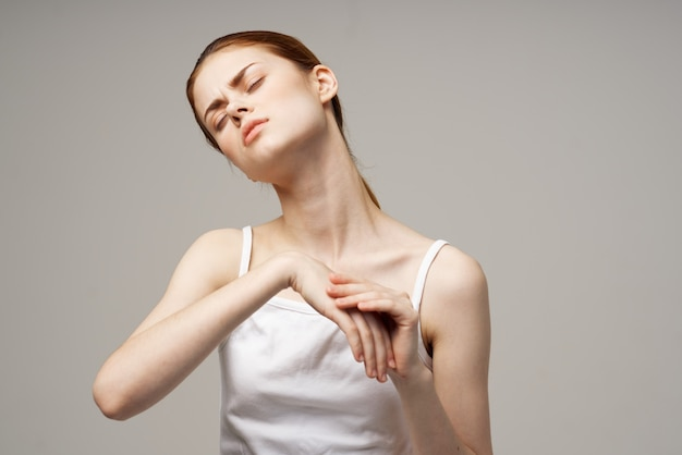 Woman in white tshirt rheumatism arm pain health problems isolated background