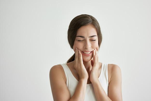 Woman in white tshirt teeth pain dentistry discomfort