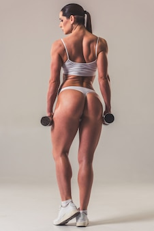 Woman in white underwear with dumbbells