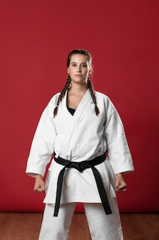 Woman in white uniform and black belt looking at camera