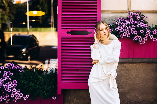 Woman in white vintage dress on the street with purple windows behind