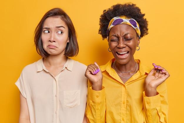 우울한 표정을 짓고 있는 여성은 노란색으로 격리된 불쾌한 일이 발생한 후 손을 들고 화를 내고 부정적인 감정을 표현합니다.