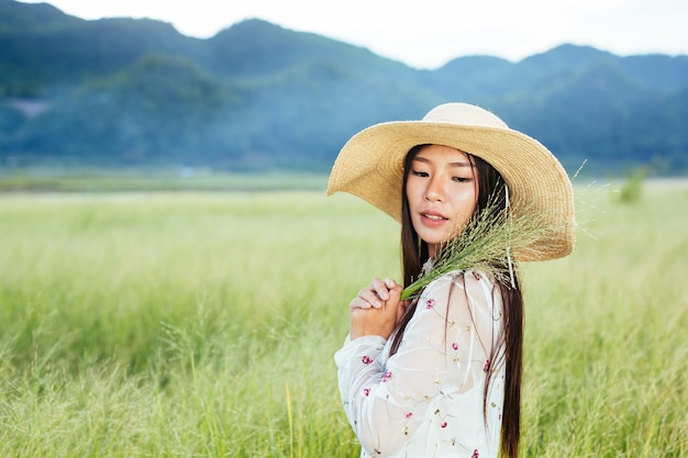 A woman who is holding a grass in her hands on a beautiful grass field with a mountain .