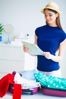 Женщина, которая готовится к отдыху. молодая красивая девушка сидит на кровати и держит в руках карту.