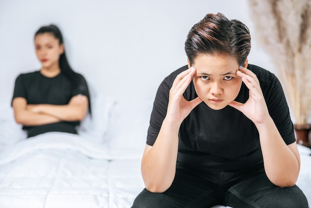 A woman who loves each other gets angry and sits on the bed.