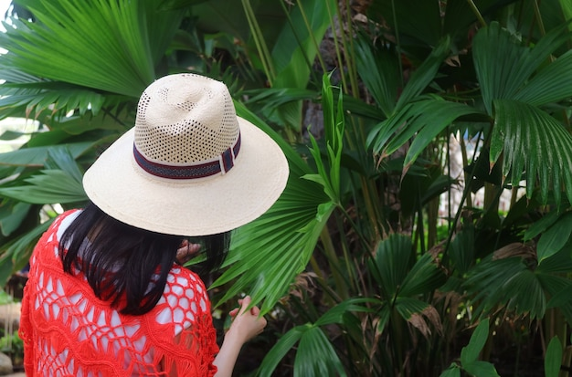 Woman in wide brim hat touching the leaf of panama hat palm plant