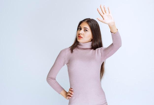 여자는 손을 크게 벌리고 무언가를 멈추고 있습니다.