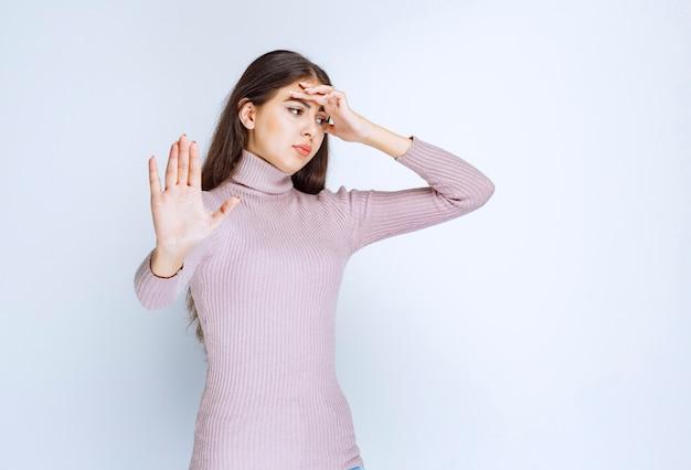 Женщина широко раскрывает руки и что-то останавливает.