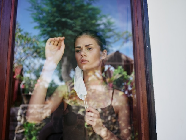 Woman in the window wearing a medical mask ban quarantine