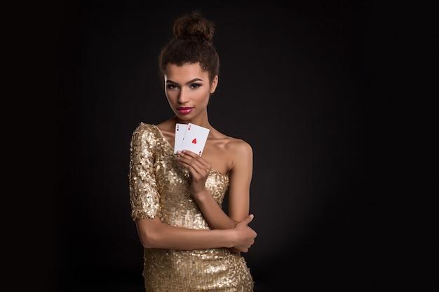 2つのエースを持っている上品なゴールドのドレスで若い女性を獲得した女性はエースカードの組み合わせのポーカー