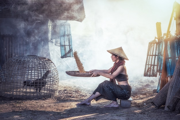 Woman winnowing rice separate between rice and rice husk