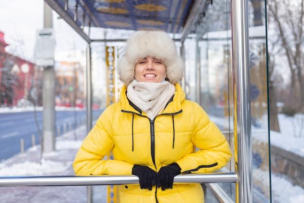 Donna in abiti invernali in una fredda giornata in attesa di un autobus a una fermata dell'autobus