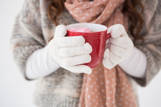 Woman in winter clothes holding a mug