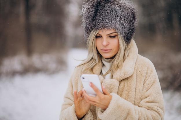 Donna in cappotto invernale che cammina nel parco pieno di neve parlando al telefono