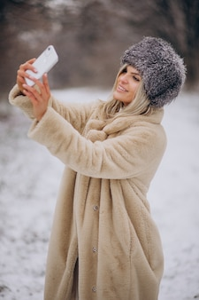 Woman in winter coat walking in park full of snow talking on the phone