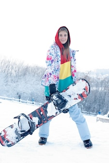 Woman winter outdoor snowboarding concept. young woman holding snowboard on her shoulders, she's looking away and smiling, copy space, close up