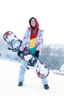 여자 겨울 야외 스노우보드 개념입니다. 그녀의 어깨에 스노우보드를 들고 있는 젊은 여성, 그녀는 멀리 보고 웃고, 공간 복사, 클로즈업
