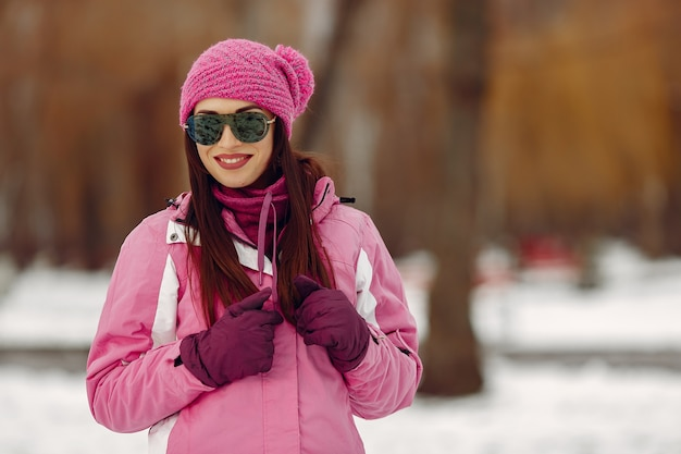 Woman in a winter park. lady in pink sportsuit. girl in a sunglasses.