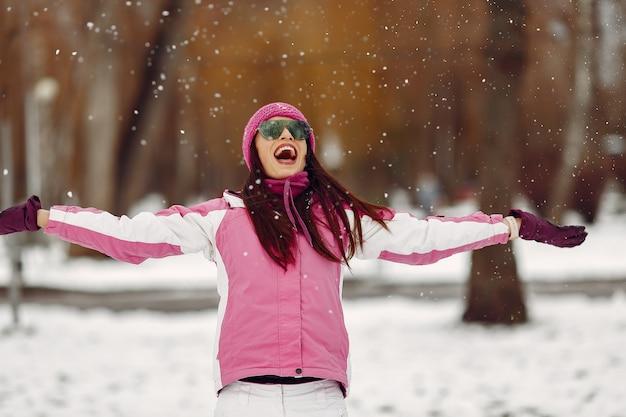 La donna in un parco d'inverno. signora in tuta sportiva rosa. ragazza in occhiali da sole.
