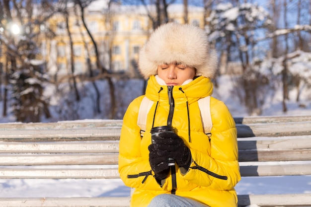 A woman in winter in warm clothes in a snow-covered park on a sunny day sits on a bench and is freezing from the cold, is unhappy in winter, holds coffee alone