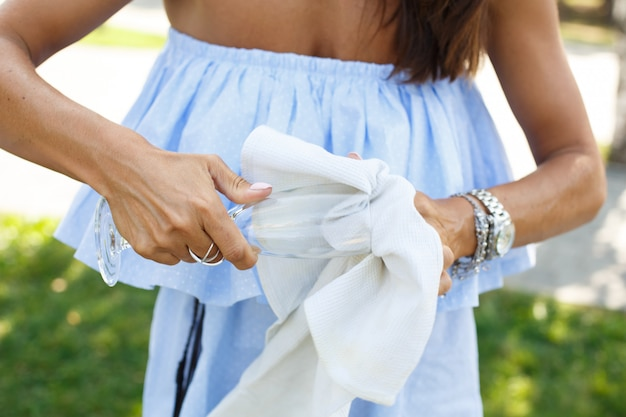 Woman wipe champagne glass sitting on green grass prepare to outdoor picnic