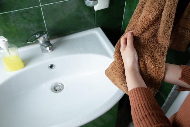 여자는 수건으로 손을 닦아