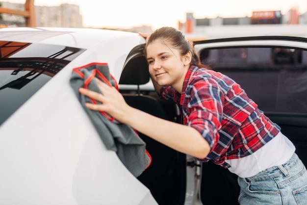 Женщина вытирает автомобиль, автомойка самообслуживания