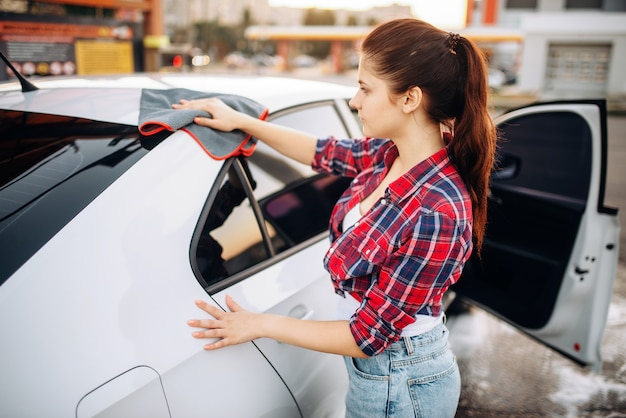 Woman wipes the car with a cloth after washing, polishing process on self-service car-wash. lady cleaning vehicle