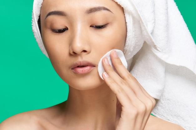 女性はコットンパッドで顔を拭きます裸の肩きれいな肌緑の背景。高品質の写真