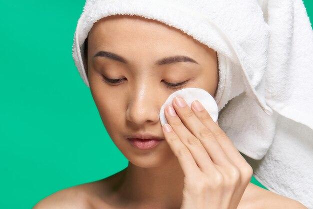 女性はコットンパッドで顔を拭きます裸の肩はきれいな肌を緑にします
