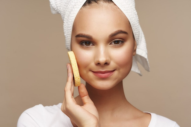 여자는 베이지색 머리 배경에 부드러운 스폰지와 수건으로 얼굴을 닦습니다. 고품질 사진