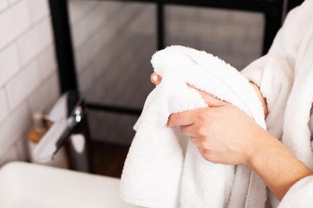 Женщина вытирает руки полотенцем в светлой ванной комнате.