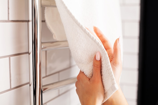 Woman wipes her hands in a towel in a bright bathroom